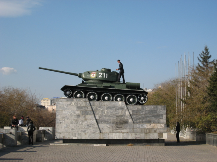 Man climbs on a tank in a park