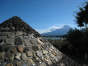 Stone model of Mount Fuji, with the mountain itself in the background