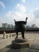 An old incense burner with modern Seoul in the background